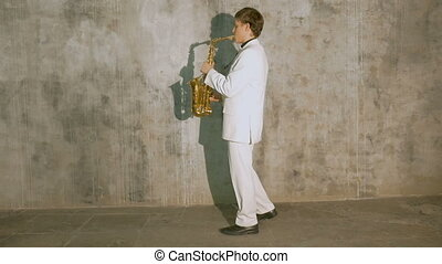 A musician in a white suit plays the saxophone.
