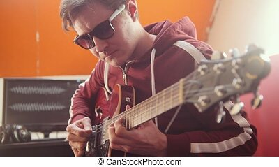 A musician man in headphones and glasses playing guitar and...