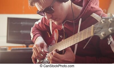 A musician man in headphones playing guitar in the studio