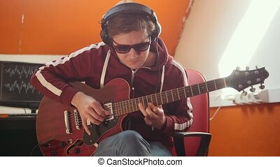 A musician man in headphones working in the studio. Playing guitar