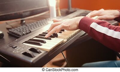 A musician man playing music on a MIDI-keyboard in the sound studio