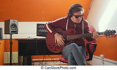 A musician man working in the sound studio. Putting on...