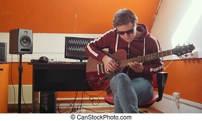 A musician man working in the sound studio. Tuning the...
