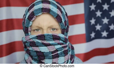 A Muslim boy on the background of the American flag