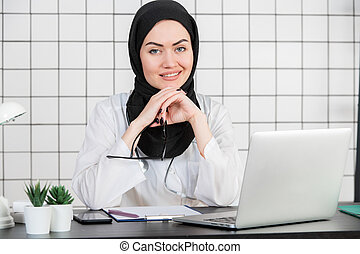 A Muslim Doctor smiling with glasses and stethoscope and documents on a white office background