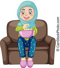 A muslim girl eating popcorn