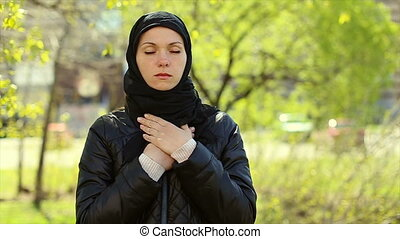A Muslim reads a prayer with her hands folded over her chest...