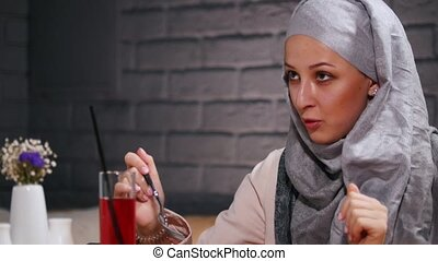 A muslim woman sitting in a restaurant eating salad....