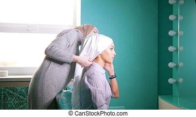 A Muslim woman tying the hijab for muslim bride - A Muslim...