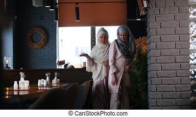 A muslim woman walking around the restaurant. Front view
