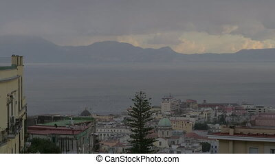 A top view of Naples city with mountains on the background and speeded up clowds, shielding ang opening the sun