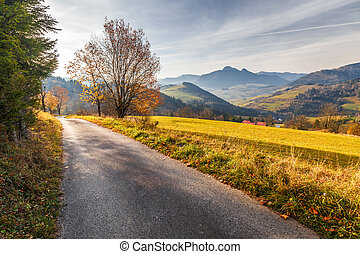 A narrow road through an autumn landscape with mountains at sunr