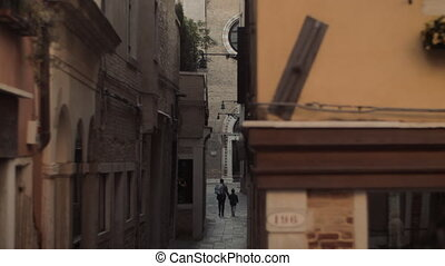 A narrow Venice street with stone facades and a paved cover...