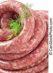 a natural raw sausage on white with spices and herbs