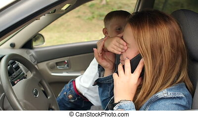 A naughty child indulges in a car, he prevents his mother from talking on phone.
