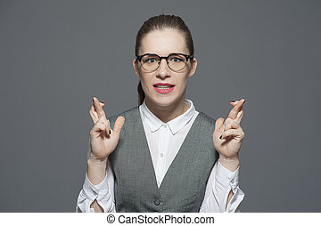 A nervous businesswoman with crossed fingers