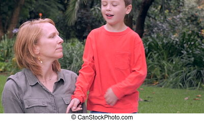A nervous mother is concerned while her son touches her shoulders - slowmo