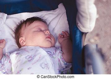 a new born boy sleeping on the carriage