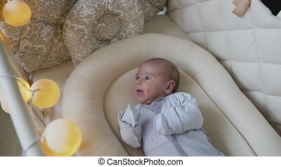 A newborn baby boy in blue baby sliders is lying in the crib at home in bedroom. Baby boy trying to fall asleep in cot. Two-month baby boy
