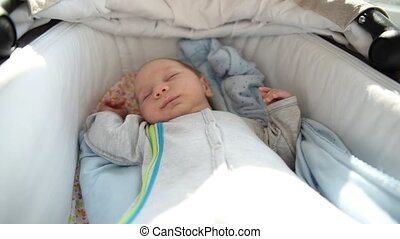 A newborn baby calmly sleeping in the cot