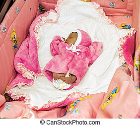 A newborn baby in pink clothes sleeps in a crib