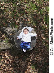A Newborn baby laying in the autumn park