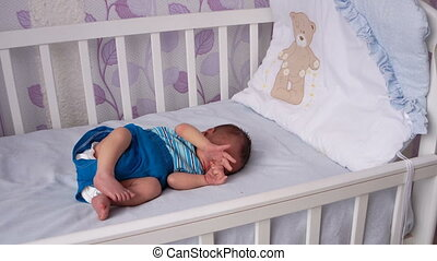 A newborn baby lies in the crib