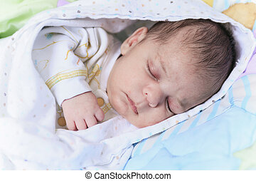 A newborn baby sleep in a crib