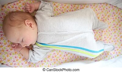 A newborn baby sleeping in the baby cot