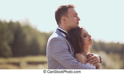A newly married couple on their wedding day amongst the green nature next to the lake. They are together in the arms of the flight. Happy together. Love. Summer.