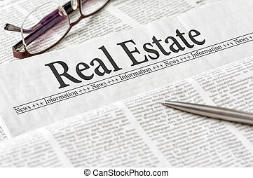 A newspaper with the headline Real Estate