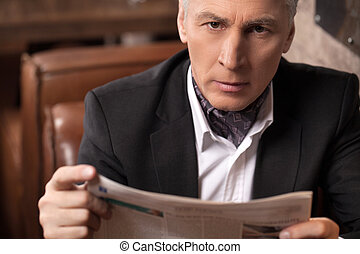 A newsworthy businessman. Confident mature businessman looking at camera and holding a newspaper while sitting in the restaurant