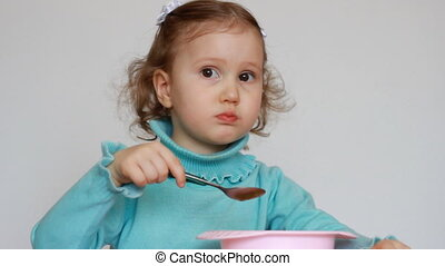 A nice little girl is sitting at a table and eating food with a spoon from a plate. The child chews carefully. Breakfast lunch dinner