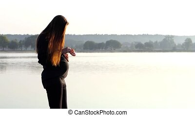 a Nice Pregnant Woman Dances With Baby's Slippers at Sunset in Autumn in Slo-Mo
