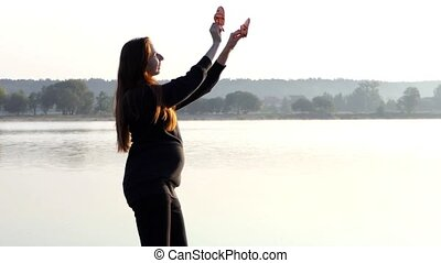 a Nice Pregnant Woman Plays With Baby`s Slippers at Sunset in Autumn in Slo-Mo