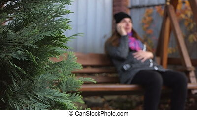 A nice pregnant woman sways on a wooden bench in slo-mo