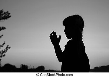 silhouette of a little girl praying