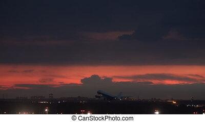 A night plane takeoff on a dark red sky background