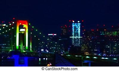 A night timelapse of miniature Rainbow bridge at the urban city in Tokyo tiltshit panning