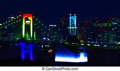 A night timelapse of miniature Rainbow bridge at the urban city in Tokyo tiltshit tilting