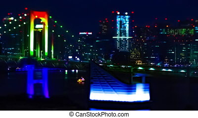A night timelapse of miniature Rainbow bridge at the urban city in Tokyo tiltshit zoom