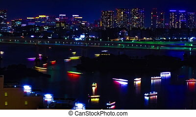 A night timelapse of ships at Rainbow bridge at the urban city in Tokyo middle shot