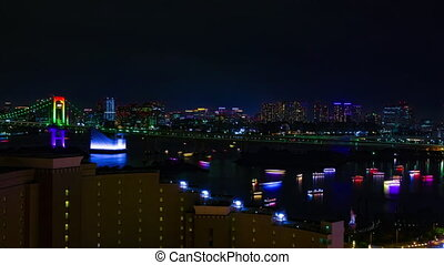 A night timelapse of ships at Rainbow bridge at the urban city in Tokyo wide shot