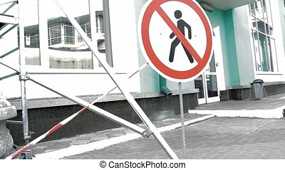 A no-Pass sign with  crossed person stands outside a building on a fenced area, on a Sunny, windy summer day in the open air. Video HD