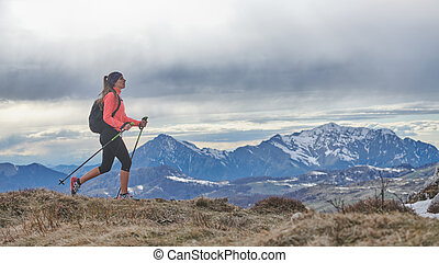 A Nordic walking girl walking alone in the mountains