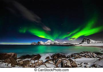 A Northern lights explotion. A raging Lady Aurora performing an amazing light show above Mt Himmeltindene in Lofoten island