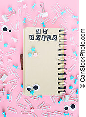 A notepad with brown pages lies in the center of the clutter of office supplies. In the notebook there is an inscription My Goals from white letters on black squares. Picture on a pink background.