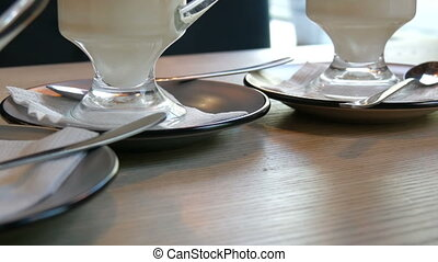 A number of glasses with coffee latte stand on a saucer on a...