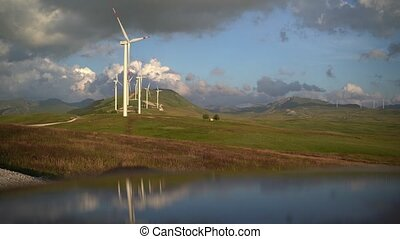 A number of wind turbines on green hills in the mountains of Montenegro, against the cloudy rainy sky.