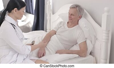 A Nurse Examines a Gray Haired Patient in His VIP Ward. - In...